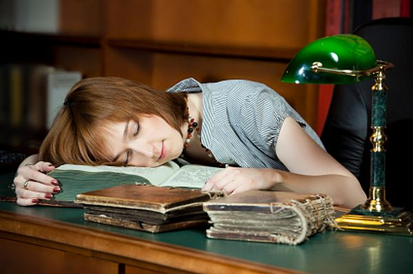Young woman sleeping on old books at the library